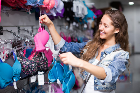 young woman in underwear: Attractive young girl selecting underwear in shopping center