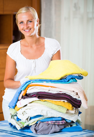 sorting: Happy young woman sorting out laundry at home and smiling Stock Photo
