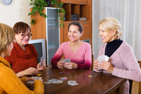 game play: Happy mature female having fun with pack of cards indoor