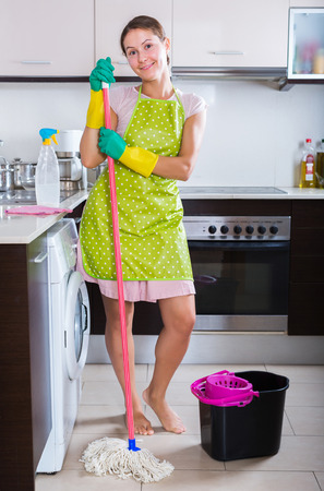 charwoman: Smiling adult brunette with mop and bucket in domestic interior Stock Photo