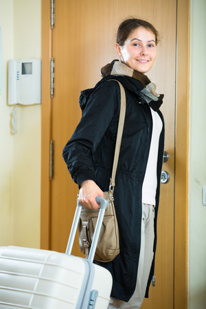 interphone: Portrait of excited female leaving home for vacation indoors