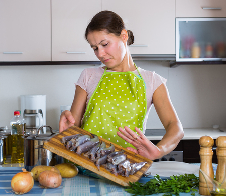 stinks: european female with foul fish that stinks in domestic interior Stock Photo