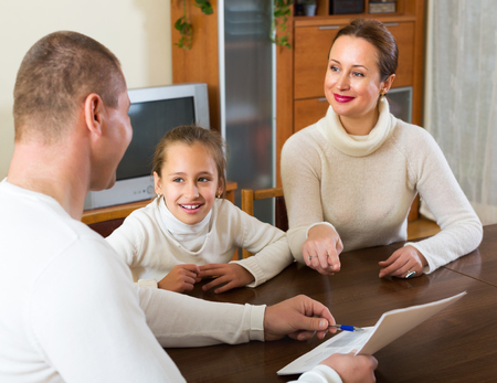 outreach: Parent and smiling daughter answer questions of outreach worker at home