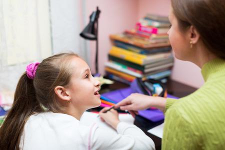 colegiala: Pequeña colegiala con la madre haciendo los deberes en casa juntos
