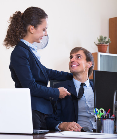 tempter: Sexual harassment in office: female flirting with employee and smiling