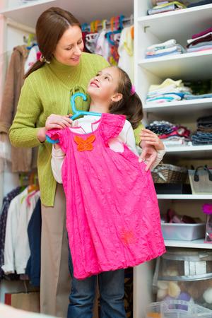 cloakroom: Preschooler smiling girl with mom choosing apparel in cloakroom