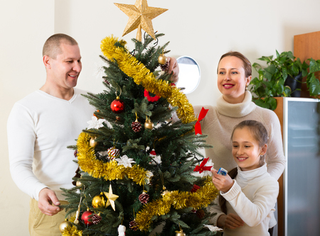 decorating christmas tree: Happy parents and girl decorating Christmas tree at living room. Focus on girl