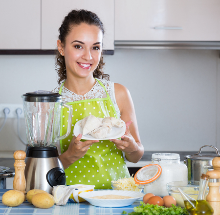 liquidiser: Portrait of happy girl making delicious croquettes using blender at home Stock Photo
