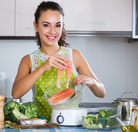 corcovado: Portrait of positive brunette girl preparing fish and veggies in steamer