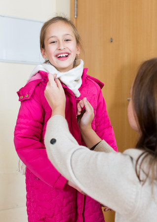 warmly: Loving and careful woman dressing her daughter warmly before off