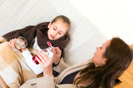 cough medicine: Mother cares after her sick daughter. She gives her a cough syrop medicine