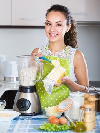 liquidiser: Smiling girl preparing pate with kitchen blender indoors Stock Photo