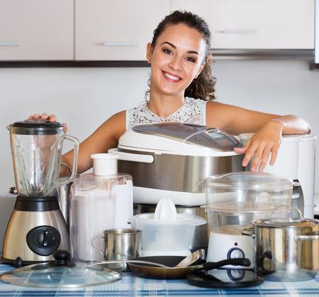 Gelukkige huisvrouw thuis met keukenapparatuur