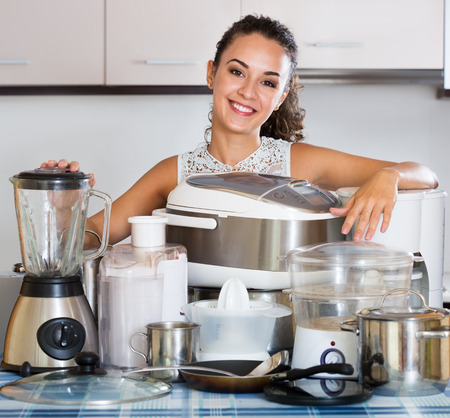 Happy housewife with kitchen appliances at home Stock Photo