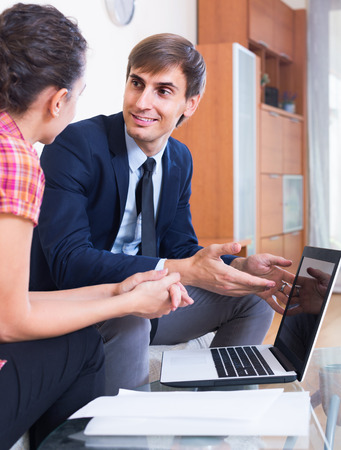 conduction: adult european insurance agent and customer discussing agreement terms and smiling Stock Photo