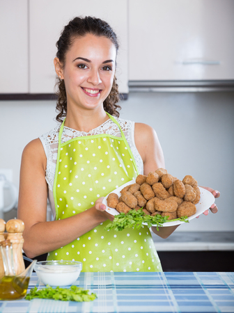 crocchette: Portrait of beautiful brunette with home-made croquettes indoors Stock Photo