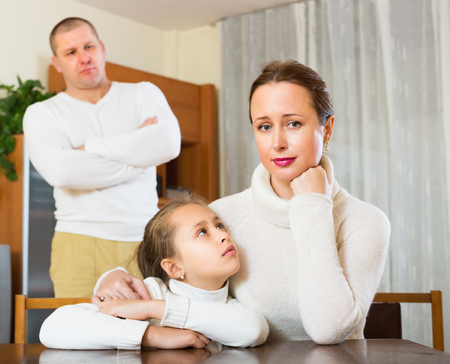 home comforts: Daughter comforting sad mother and angry father Stock Photo