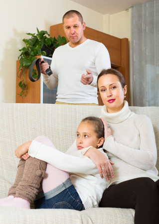 fracas: Serious dad berating sad little daughter in home interior. Focus on woman Stock Photo