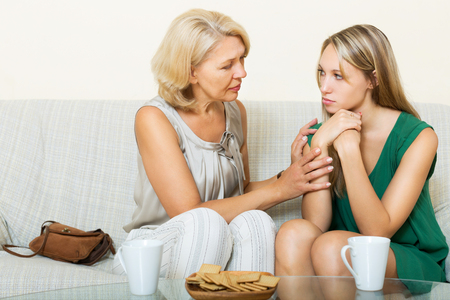 home comforts: Mature mother consoles   daughter at home