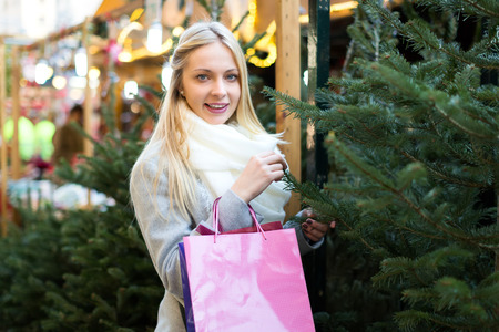 lifestile: Smiling beutiful young blonde inspecting fir on a Christmas fair Stock Photo
