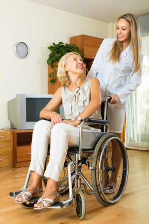 incapacitated: Friendly physician and positive disabled female on chair communicating indoor