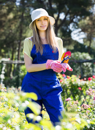 woman gardening: Smiling  gardener in uniform working in the garden