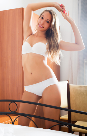 stretchy: Happy blonde girl wearing white stretching  at bedroom