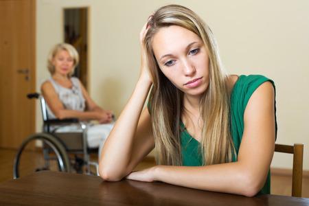 paraplegico: Muchacha cansada y persona con discapacidad en silla de interior