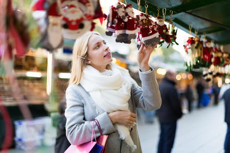 overspending: Beautiful long-haired blonde girl choosing Christmas decoration at market