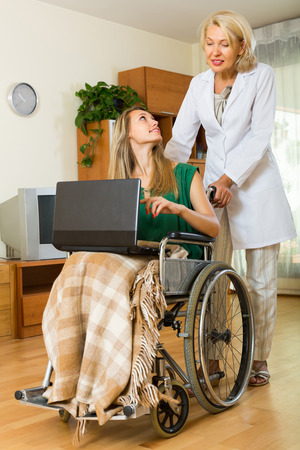 incapacitated: Adult social worker and disabled young woman on chair with laptop. Focus on girl Stock Photo