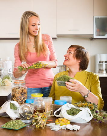 concoct: Aged mother and adult daughter with herbal tea and herbs in domestic kitchen
