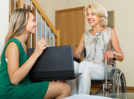 incapacitated: Social worker with laptop questioning handicapped elderly woman. Focus on mature Stock Photo