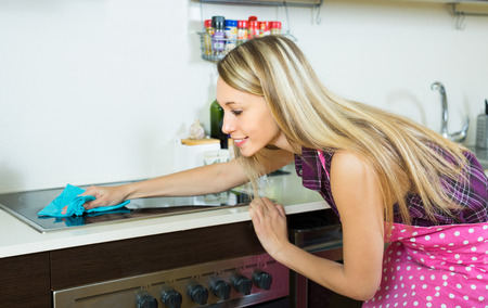 stay home work: Smiling young blonde woman cleaning electric panel with rag and cleanser