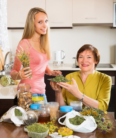 heterogeneous: Happy mature woman with daughter with dried herbs