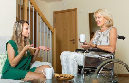incapacitated: Happy elderly women in wheelchair and girl drinking tea at home. Focus on mature Stock Photo