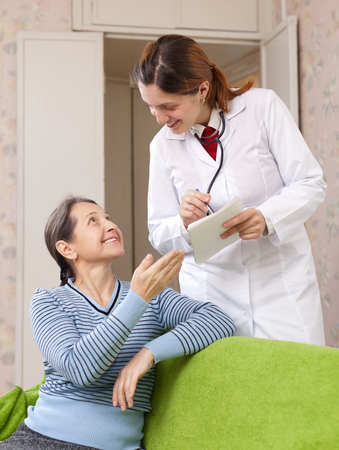 malaise: joyful mature woman tells the doctor the symptoms of malaise on couch