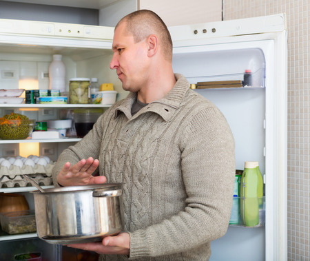 foul: Man holding foul  bed food near refrigerator at kitchen Stock Photo