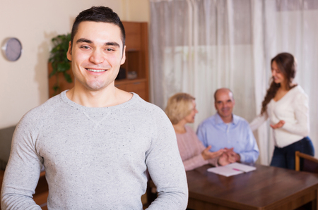 hypothec: happy guy and big family with agent at distance indoor