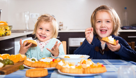 whipped cream: Happy healthy smiling children eating pastry in the kitchen of their house