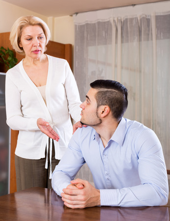 adult intercourse: Young guy and his mature girlfriend having serious conversation indoors. Focus on the man Stock Photo