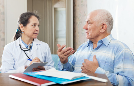 complaining: senior man  complaining to serious doctor about malaise in interior Stock Photo