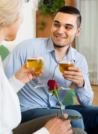 mismatch: Smiling adult son congratulating happy mother and proposing a toast Stock Photo
