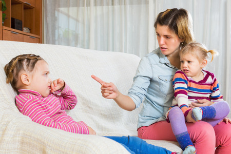 berate: Young angry mother sitting on sofa and scolding little daughter Stock Photo
