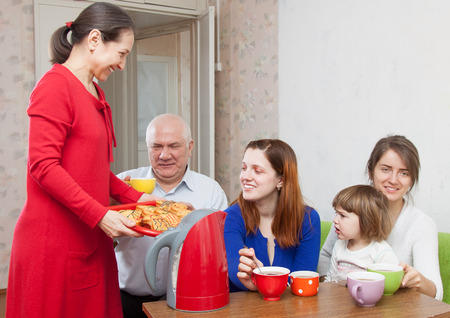 multigeneration: multigeneration family communicate over tea with cakes at home