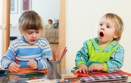 gladful: siblings playing with pencils in home Stock Photo