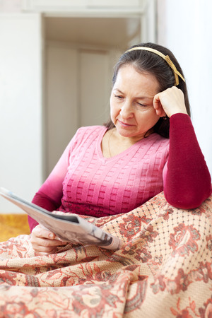 wistful: wistful woman reading newspaper at home