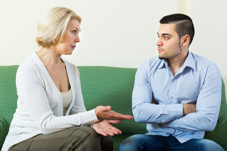 mismatch: Aged woman and young boyfriend discussing something with serious faces on sofa
