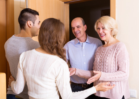 young couple inviting elderly parents to come inside
