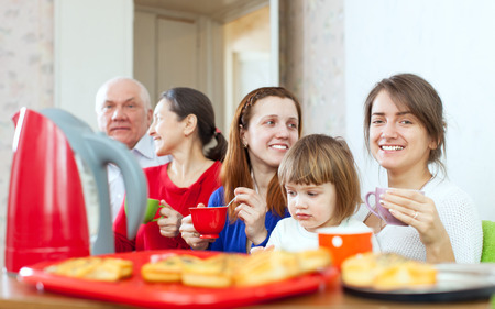 multigeneration: happy multigeneration family communicate over tea with cakes