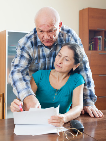 fills: Mature woman fills documents, man helps her at home